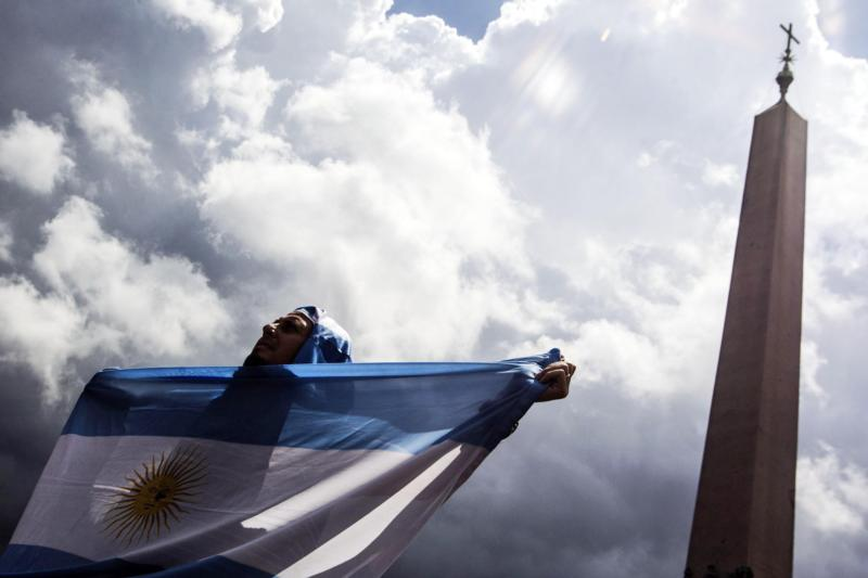A man holds an Argentine flag at the Vatican in this July 13, 2014, file photo. The sainthood cause of Argentine Cardinal Eduardo Francisco Pironio, who organized the first World Youth Days as president of the Pontifical Council for the Laity, has been forwarded to the Vatican. (CNS photo/Angelo Carconi, EPA)