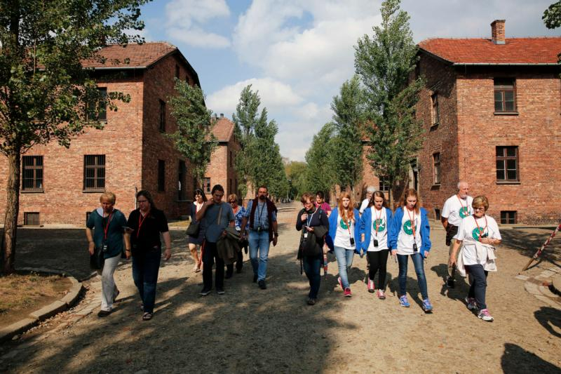 Visitors walk between Auschwitz I cellblocks as they tour the Auschwitz-Birkenau Memorial and State Museum in Oswiecim, Poland. The Auschwitz memorial and museum is setting aside days exclusively for World Youth Day pilgrims who want to tour the former Nazi death camp. (CNS photo/Nancy Wiechec)