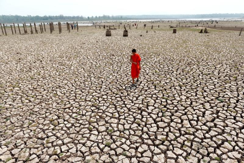 A Buddhist novice monk walks on parched land in Lampang, Thailand, March 12. (CNS photo/Rungroj Yongrit, EPA)