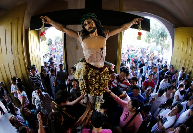 """Filipinos touch a cross during an Ash Wednesday ceremony in a suburb of Manila, Philippines, Feb. 10. Pope Francis says the """"crucifix is not a decoration"""" but that redemption is possible because Jesus took on the sins of the world. (CNS photo/Francis R. Malasig, EPA)"""