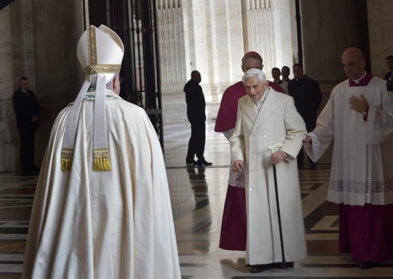 """Retired Pope Benedict XVI prepares to greet Pope Francis during the opening of the Holy Door of St. Peter's Basilica at the Vatican in this Dec. 8, 2015, file photo. In a written interview, the retired pope commented on the theme of mercy. """"Mercy is what moves us toward God, while justice makes us tremble in his sight, Pope Benedict said. (CNS photo/Stefano Spaziani, pool)"""
