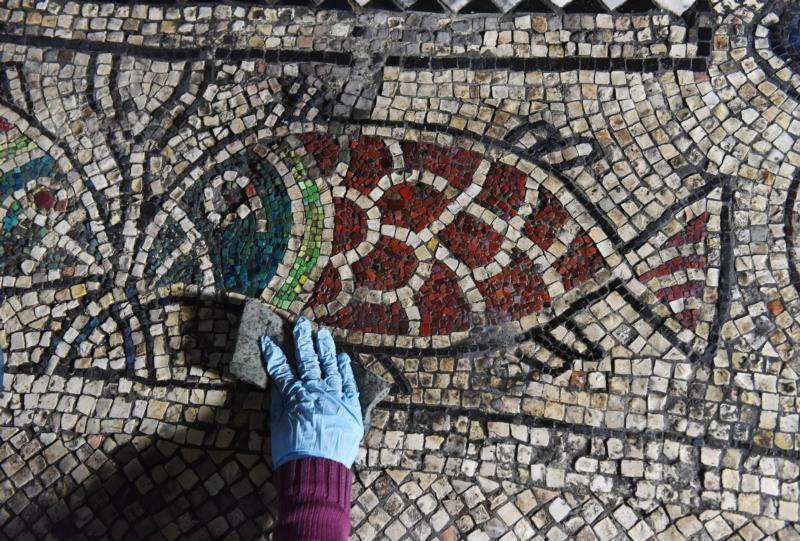 A student from the Jericho Mosaic Center cleans a mosaic in the Franciscan section of the Church of the Holy Sepulcher in the Old City of Jerusalem March 17. (CNS photo/Debbie Hill)