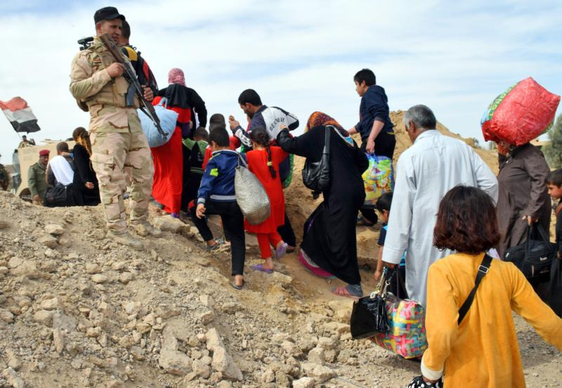 """Iraqi soldiers observe the evacuation of families from the recently recaptured town of Zangura, Iraq, March 9. The British government has defeated an attempt to recognize the """"genocide"""" of religious minorities by the Islamic State. (CNS photo/Nawras Aamer, EPA)"""