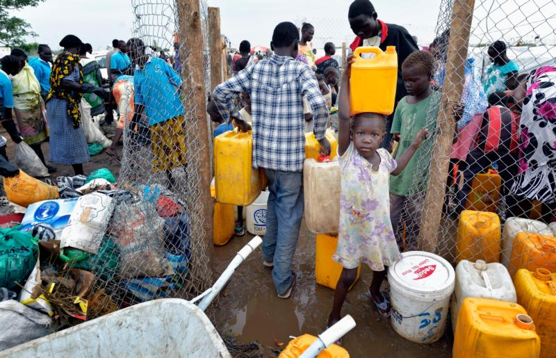 A girl carries water from a communal water distribution site in 2014 inside a camp for internally displaced families in Juba, South Sudan. South Sudan's economy is near collapse, its church leaders said as they urged its warring parties to stop the conflict and form a unity government. (CNS photo/Paul Jeffrey)