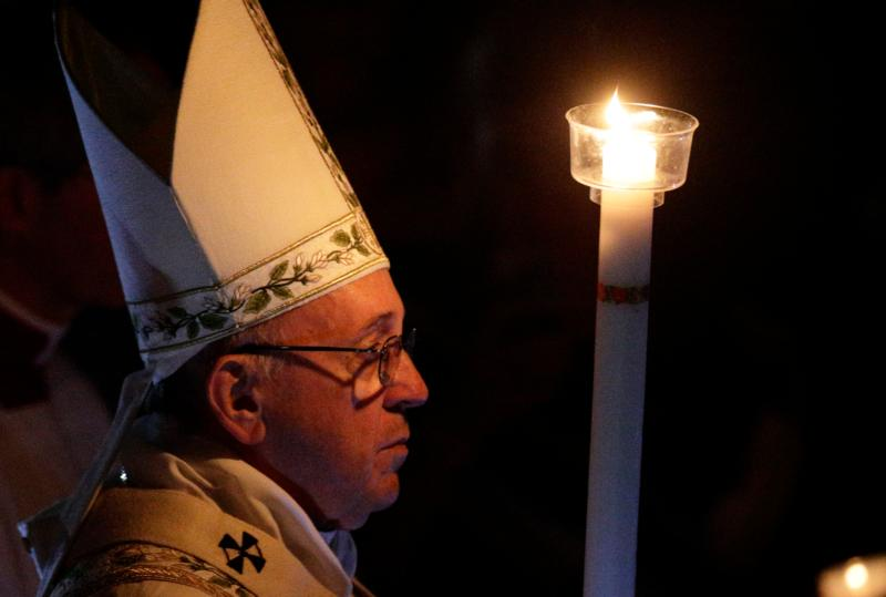 Pope Francis carries a candle in procession as he arrives to celebrate the Easter Vigil in St. Peter's Basilica at the Vatican March 26. (CNS photo/Paul Haring)