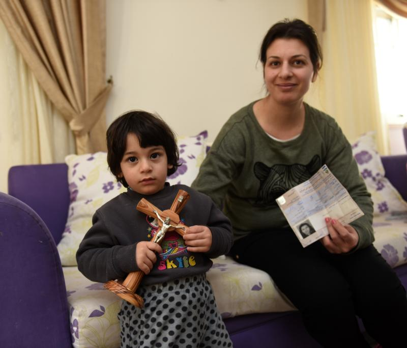 Nivine Sansour holds her permit from the Israelis to travel to Jerusalem for Holy Week alongside her 2-year-old son, Elia, in their home March 24 in Beit Jalla, West Bank. Nivine's husband, Nicola, did not receive a permit from the Israelis to travel from the West Bank to Jerusalem for Easter. (CNS photo/Debbie Hill)