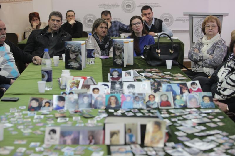 Victims' pictures are displayed on a table in Sarajevo, Bosnia-Herzegovina, as people watch a TV broadcast of an international tribunal in the Netherlands March 24. Radovan Karadzic, a former Bosnian Serb leader, was convicted of genocide and nine other charges for orchestrating a campaign of terror that left 100,000 people dead during the 1992-95 war in Bosnia-Herzegovina. (CNS photo/CNS photo/Fehim Demir, EPA)