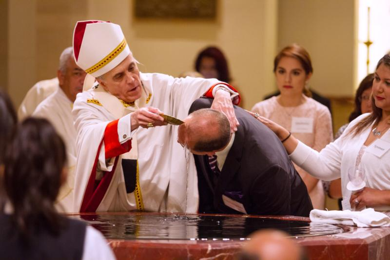 Cardinal Daniel N. DiNardo of Galveston-Houston baptizes a catechumen during the Easter Vigil at the Co-Cathedral of the Sacred Heart in Houston March 26. (CNS photo/James Ramos, Texas Catholic Herald)