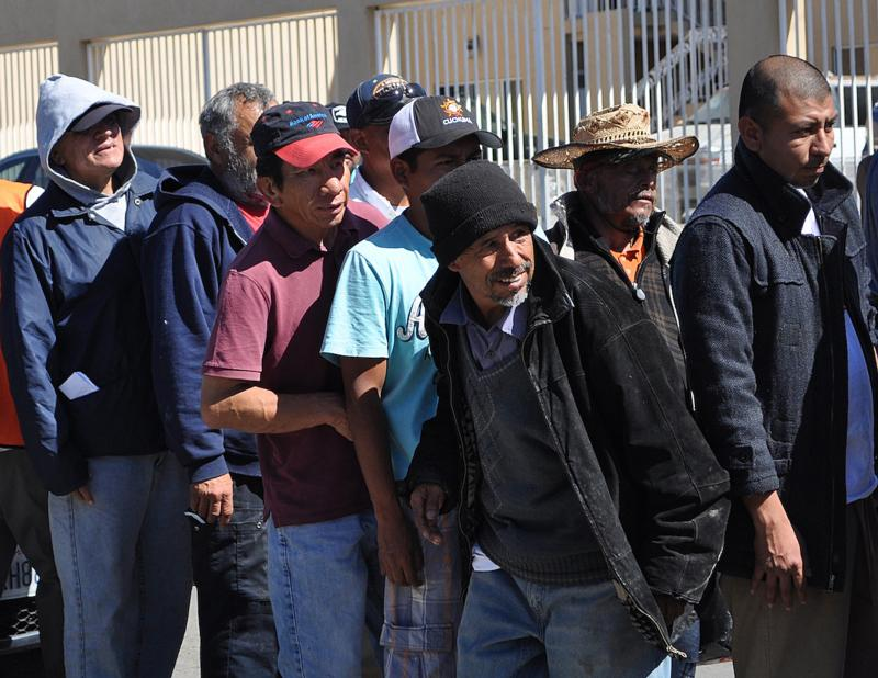 Migrant men are seen in an undated photo lining up outside Instituto Madre Assunta for a meal in the city of Tijuana in Mexico. Heber Marin Velasquez from Vera Cruz, second from right, was deported from the U.S. in February. (CNS photo/J. Malcolm Garcia, GSR)