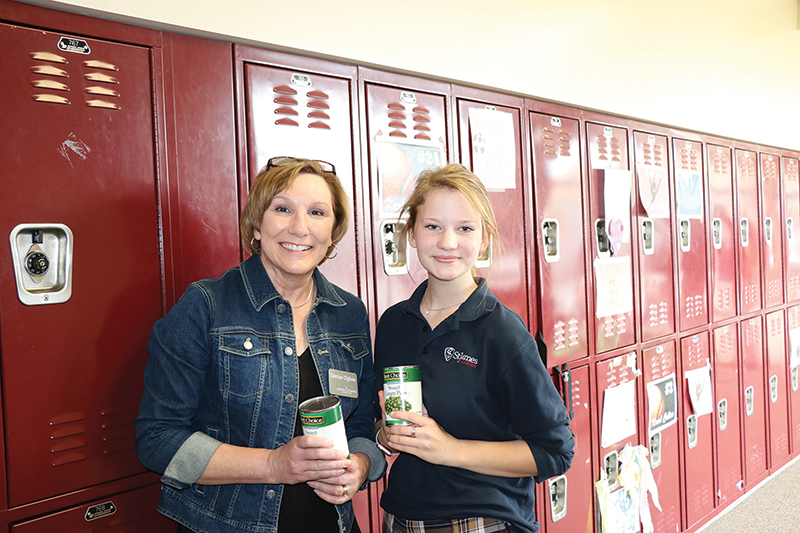 Denise Ogilvie, right, Catholic Charities director of outreach, meets with Sister Bridget Martin, FSGM, at a canned food drive at St. James Academy in Lenexa.