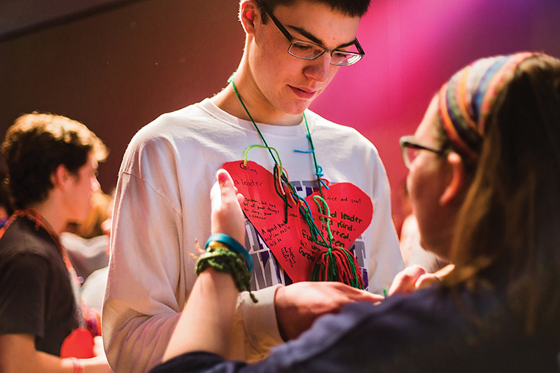 "Evan Johnson, a junior at St. James Academy, Lenexa, exchanges ""warm fuzzies"" with a fellow leader, an activity in which the retreatants give one another affirmations. The heart he is wearing was made by his small group."