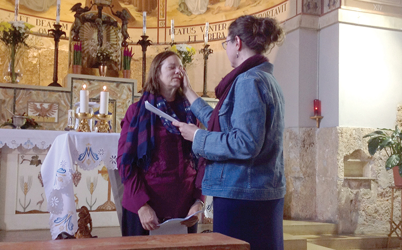 Sharri Orndorff, left, takes part in the Rite of Acceptance during a pilgrimage to the Church of the Visitation at Ein Kerem, Israel. Denise Bossert, a Catholic author who became Orndorff's mentor, was her sponsor for the event. Orndorff was inspired to become Catholic after seeing a quote pinned by Bossert on the social media site Pinterest, to the right.