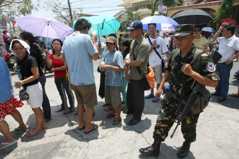 A Philippine air force trooper walks past voters lining up outside a precinct on election day in 2010 in Las Pinas. Archbishop Socrates Villegas of Lingayen-Dagupan is urging Catholics to heed the Ten Commandments before they head to the polls in May to vote for offices ranging from president to local village councilors. (CNS photo/Rolex Dela Pena, EPA)