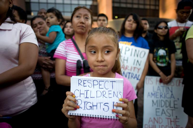 A girl holds a sign during a 2014 vigil and rally in support of the flood of undocumented Central American minors apprehended along the U.S.-Mexico border. A new report says less than 1 percent of Central American children apprehended by Mexican immigration officials are able to obtain asylum in Mexico. (CNS photo/David Maung, EPA)
