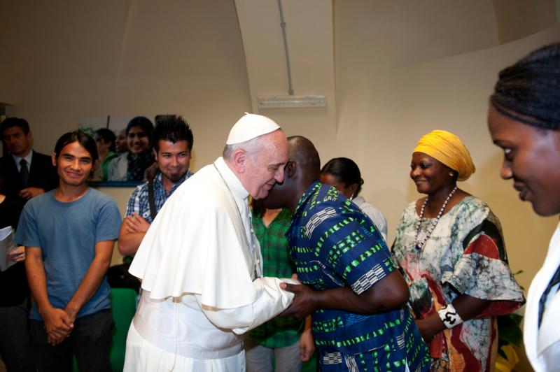 Pope Francis greets refugees during a 2013 visit to the Astalli Center of the Jesuit Refugee Service in Rome. Just months after his election that year, Pope Francis had said church buildings that no longer house nuns, friars, monks and other religious should be used to shelter refugees. (CNS photo/Alessia Giuliani, Catholic Press Photo)