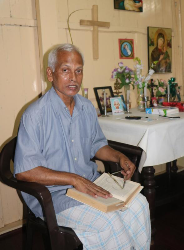 Mathew Uzhunnalil, brother of kidnapped Salesian Father Thomas Uzhunnalil, poses with his prayer book at his home in Ramapuram, India. Father Uzhunnalil was kidnapped March 4 from the home for the aged and disabled run by the Missionaries of Charity in Aden, Yemen. (CNS photo/Anto Akkara)