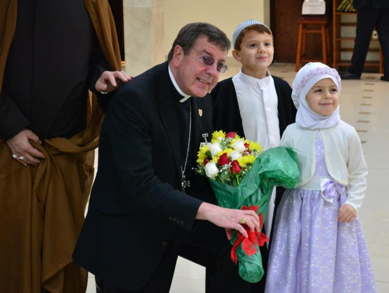 "Detroit Archbishop Allen H. Vigneron poses for a photo with a young Muslim boy and girl during a ""unity lunch"" with local Muslim leaders at the Islamic House of Wisdom in Dearborn, Mich., April 5. (CNS photo/Mike Stechschulte, The Michigan Catholic)"