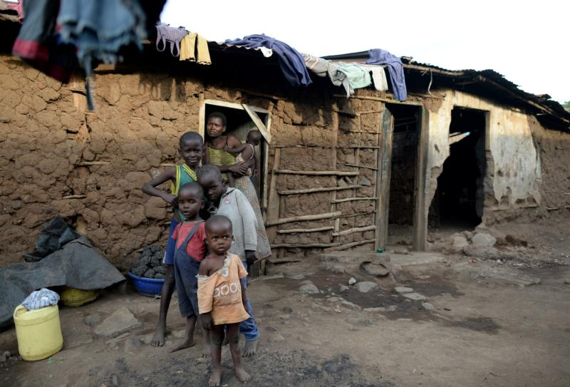A Kenyan family stands in front of their home May 6, 2014, in a Kisumu shantytown. Kenyan bishops said in a statement issued at the end of a two-day meeting at St. Thomas Aquinas Seminary that ordinary men and women are bearing the burden of corruption. (CNS photo/Roland Schlager, EPA)