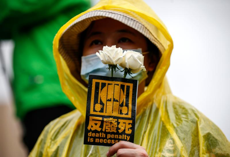 A protester holds a sticker and roses during an April 10 demonstration against the death penalty in Taipei, Taiwan. Pope Francis urged additional support in abolishing the death penalty worldwide and eradicating the external debt of developing countries. (CNS photo/Ritchie B. Tongo, EPA)