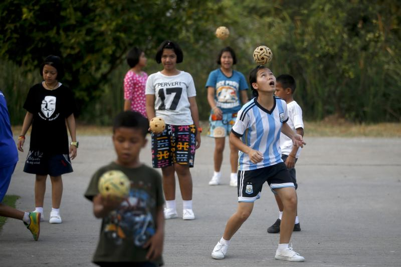 """HIV-positive youths are seen March 7 playing with soccer balls during exercise time at the Baan Dek Thammarak orphanage in Bangkok. Caritas Internationalis brought together representatives of faith-based groups from all over world April 11-13 in Rome to hammer out a """"road map"""" indicating the best ways to promote or provide early diagnosis and treatment for HIV, especially in children. (CNS photo/Diego Azubel, EPA)"""
