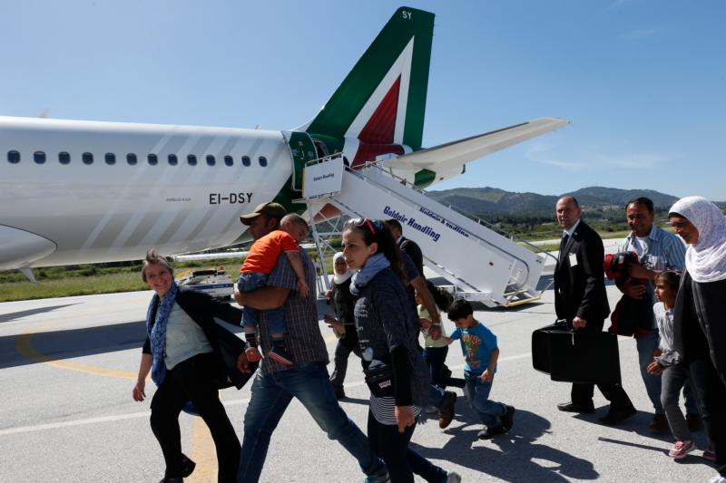 Refugees walk to board Pope Francis' plane to Rome at the international airport in Mytilene on the island of Lesbos, Greece, April 16, 2016. The pope brought 12 refugees to Italy aboard his flight. (CNS photo/Paul Haring)