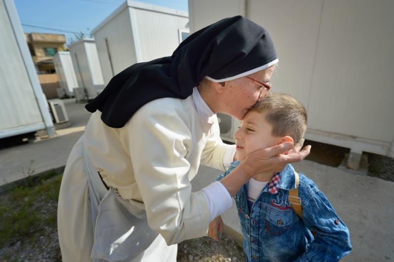 Dominican Sister Elene kisses 4-year old Luis Firas as he walks to a preschool in Ankawa, Iraq, April 7. The Dominican Sisters of St. Catherine of Siena were displaced by the Islamic State group in 2014 and have established schools and other ministries among the displaced. (CNS photo/Paul Jeffrey)