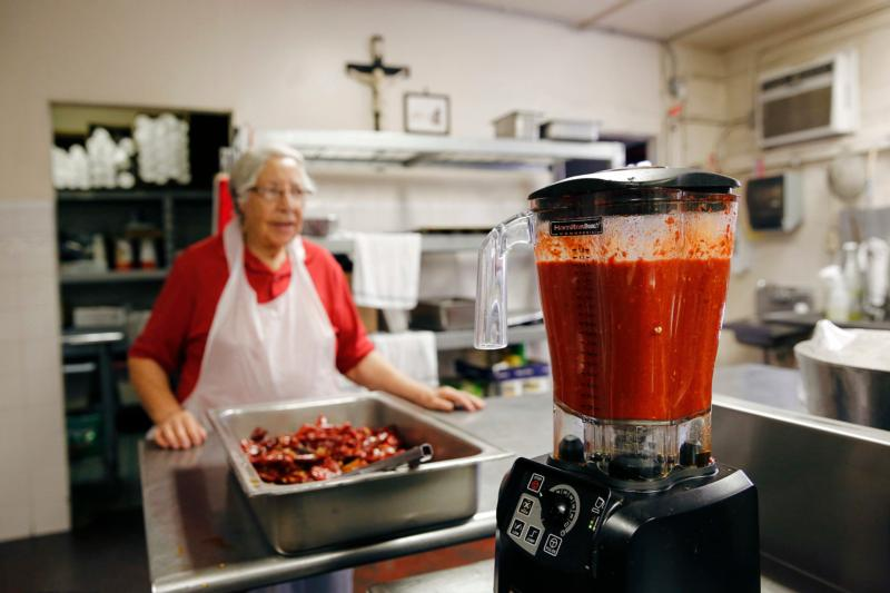 Mary Lou Murguia oversees the blending of red chiles in the kitchen of La Tilma Mexican Grill in mid-February at Sacred Heart Church in El Paso, Texas. The eatery serves up generous plates of homestyle food at value prices. (CNS photo/Nancy Wiechec)