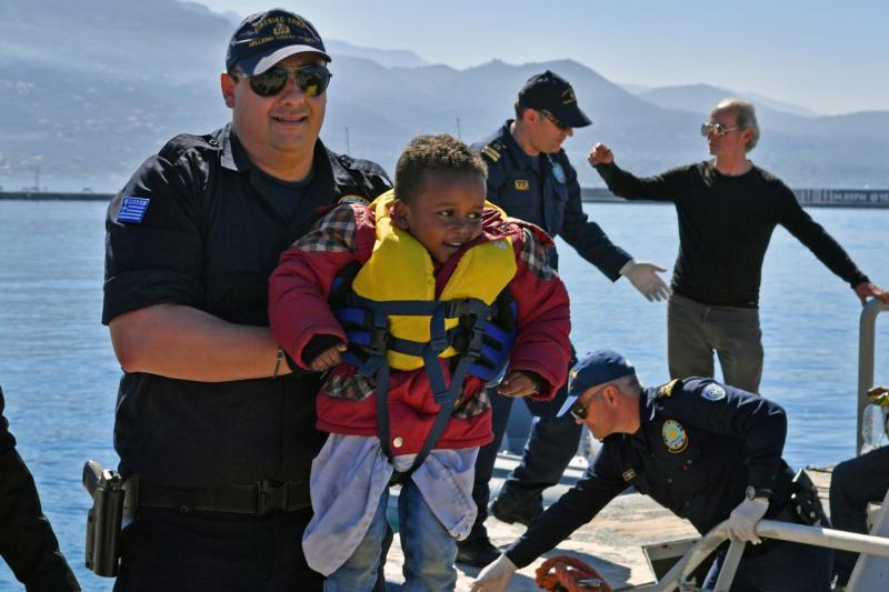 A member of the Coast Guard carries a young refugee and other survivors off a rescue boat April 17 at the port of Kalamata, Greece. The survivors told U.N. staff that they had been part of a group of between 100 and 200 people who departed from Libya the previous week. (CNS photo/Nikitas Kotsiaris, EPA)