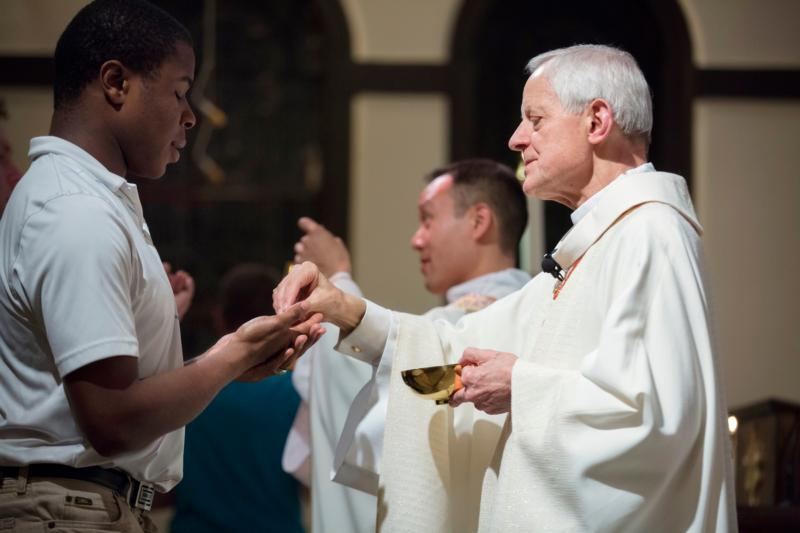 Cardinal Donald W. Wuerl of Washington gives Communion to a young man during the April 21 University Mass for Life at Epiphany Catholic Church in Washington, one day after Planned Parenthood's president, Cecile Richards, gave a speech at nearby Georgetown University at the invitation of a student-led group. (CNS photo/Jaclyn Lippelmann, Catholic Standard)