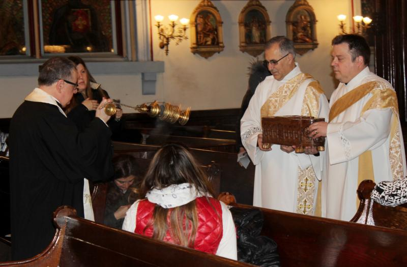 Msgr. James A. Root, rector of Our Lady of Lebanon Maronite Cathedral in Brooklyn, N.Y., uses incense April 9 as Subdeacons Peter Frangie and Norbert Vogl carry the reliquary of St. Sharbel Makhlouf. The relics were in Brooklyn April 9-10 as part of a U.S. tour to mark the 50th anniversary of the Lebanese monk's beatification. (CNS photo/Marie Elena Giossi, The Tablet)