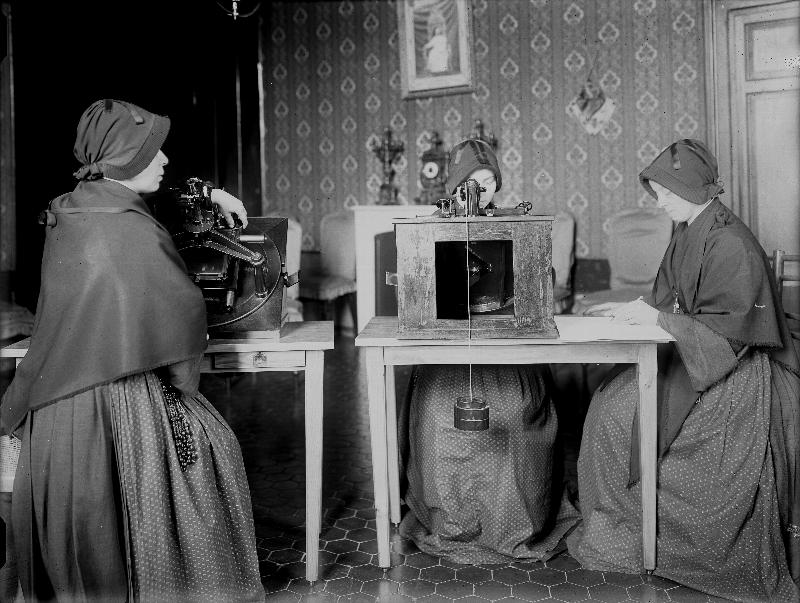 Members of the Sisters of the Child Mary use microscopes to review glass plates as they measure star positions for a collaborative photography project the Vatican participated in  to catalogue the stars and create a photographic map of the heavens. At right a member of the order records star coordinates in a ledger. Sisters Emilia Ponzoni, Regina Colombo,  Concetta Finardi and Luigia Panceri worked on recording star coordinates from glass plates between 1910 and 1921. (CNS photo/courtesy Vatican Observatory)