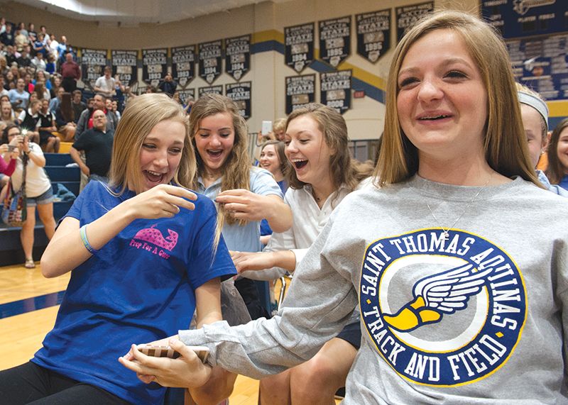 Aquinas student Maggie McCabe is shown the first strands of her hair, while Olivia Evans braces for the sound of shears. This is the ninth year Aquinas has hosted a Wigs Out event.