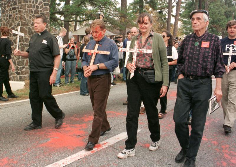 Jesuit Father Daniel Berrigan, right, and actor Martin Sheen, third from right, join the annual School of the Americas protest in 1999 at Fort Benning, Ga. Father Berrigan, an early critic of U.S. military intervention in Vietnam who for years challenged the country's reliance on military might, died April 30 at 94. (CNS photo/Quirin, The Messenger)