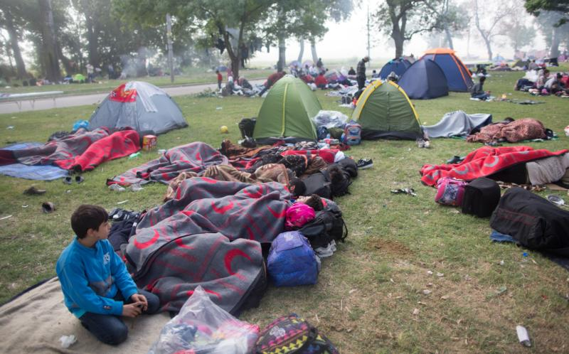 Syrian refugees rest at a in park in 2015 as they wait for permission to pass the Turkish-Greek border in Edirne, Turkey. A U.N. summit set to take place in Istanbul May 23-24 seeks more efficient, sustainable and humanitarian ways of helping the world's millions of refugees. (CNS photo/Tolga Bozoglu, EPA)