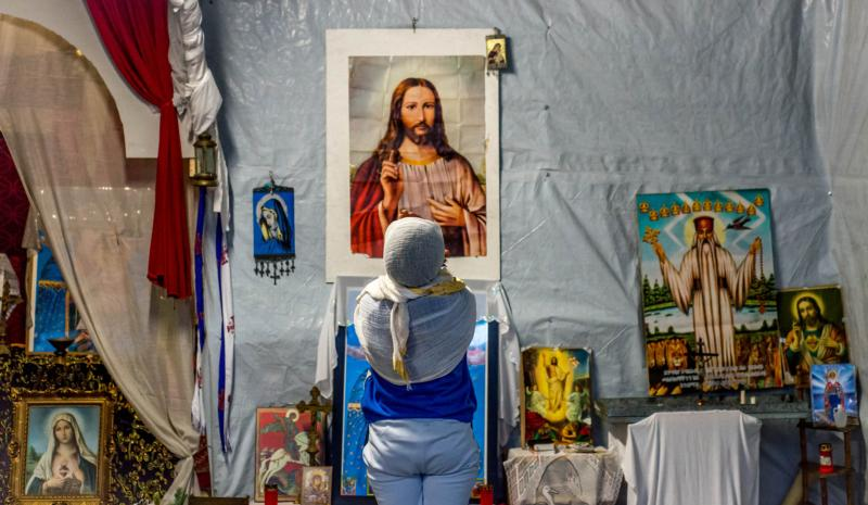 "A refugee prays in front of an image of Christ in a makeshift church in a camp called ""The Jungle"" in 2015 in the port of Calais, France. (CNS photo/Stephanie Lecocq, EPA)"