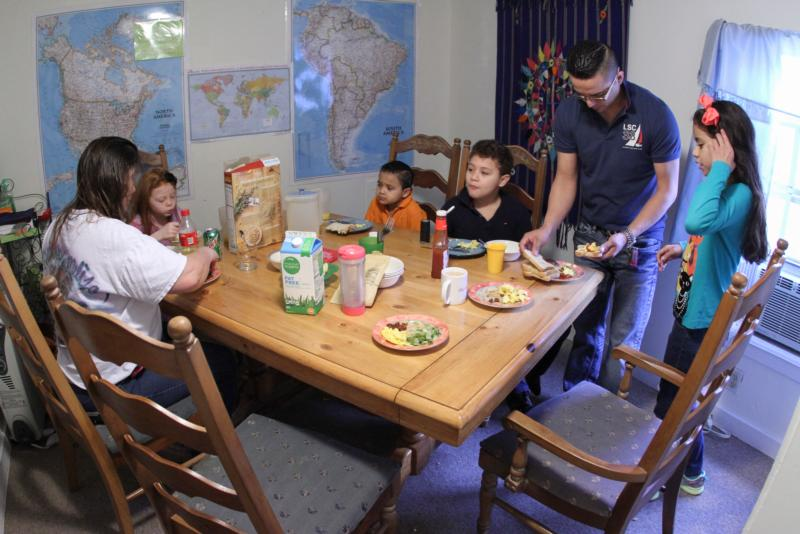 Overnight guests Melissa Sandoval and her granddaughter Hailee eat breakfast along with other guests Jared Martinez, his brother Jafet, his father Milber, and his sister Brianna, in late February at the El Refugio hospitality house in Lumpkin, Ga. Family members who stay at the house drive hundreds of miles to spend one hour visiting detainees at the nearby Stewart Detention Center. (CNS photo/Michael Alexander, Georgia Bulletin)