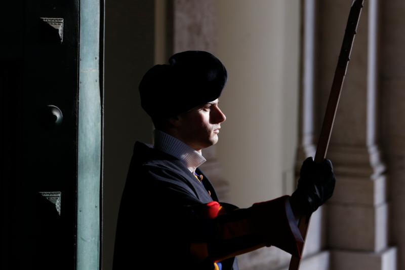 A Swiss Guard stands at the entrance to the Apostolic Palace at the Vatican in this Dec. 14, 2015, file photo. Father Thomas Widmer, chaplain of the Swiss Guard, said a guard's service is also meant to deepen his faith. (CNS photo/Paul Haring)
