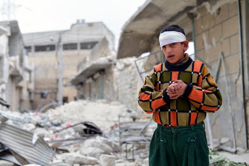 An injured boy stands amid rubble outside his home in 2014 after airstrikes in Aleppo, Syria. The Melkite Catholic archbishop of Aleppo has asked for support for his war-torn city and thanked the Knights of Columbus and other organizations for speaking out about the genocide of Syrian Christians and other religious minorities. (CNS photo/Ali Mustafa, EPA)