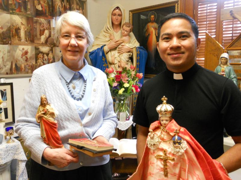 Jan Marie Shannon and Father Al Benedick Taguinod of the Missionaries of Our Lady of La Salette in the Philippines, pose with religious figures April 12 at Shannon's Tilma shop in Berea, Ohio. (CNS photo/Jerri Donohue)