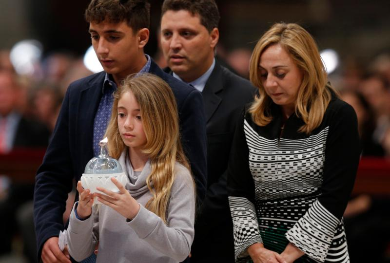 "Members of the Pellegrino family walk forward to present a candle during a prayer vigil led by Pope Francis ""to dry the tears"" of the suffering in St. Peter's Basilica at the Vatican May 5. The family lost a son and brother. Pictured are siblings Chiara and Raffaele, and parents Domenico Pellegrino and Giovanna Astarita. (CNS photo/Paul Haring)"