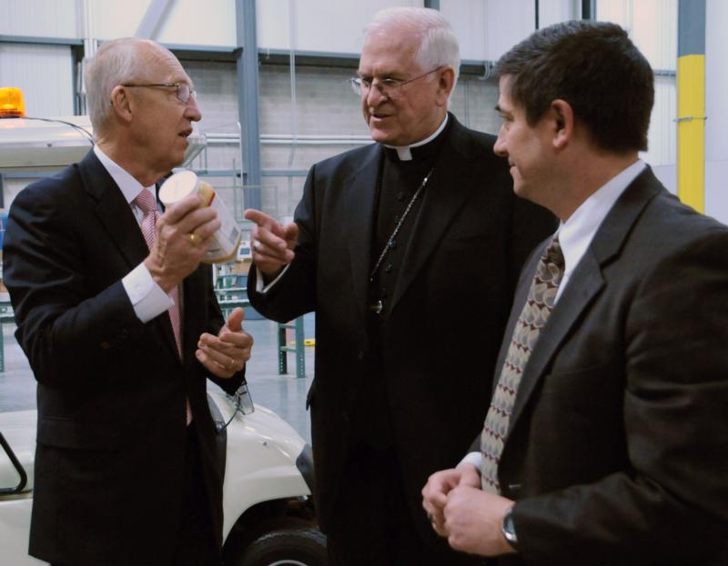 Elder Don R. Clark, of the Church of Jesus Christ of Latter-day Saints, explains to Archbishop Joseph E. Kurtz of Louisville, Ky., president of the U.S. Conference of Catholic Bishops, that much of the food the LDS Church distributes to the needy has a church label. They are shown May 4 at the LDS Church's Utah Bishops' Central Storehouse in Salt Lake City, which Archbishop Kurtz toured during a visit to Utah to meet with Mormon leaders. (CNS photo/Marie Mischel, Intermountain Catholic)
