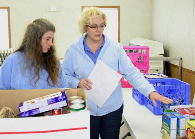 Kim Jackson, a staff member of the Catholic Charities West Virginia Wellness Works Mobile Food Pantry, helps Michelle Nicholson with food selections during the food pantry's visit to Amma, W.Va., April 25. (CNS photo/Colleen Rowan, The Catholic Spirit)