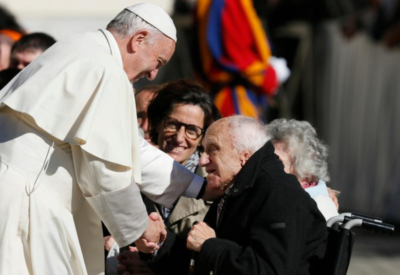 Pope Francis greets a man in a wheelchair during his general audience in St. Peter's Square at the Vatican Oct. 12. The pope called for an immediate cease-fire in Syria so that civilians can be rescued. (CNS photo/Paul Haring) See POPE-SYRIA-APPEAL and POPE-AUDIENCE-WORKS-MERCY Oct. 12, 2016.