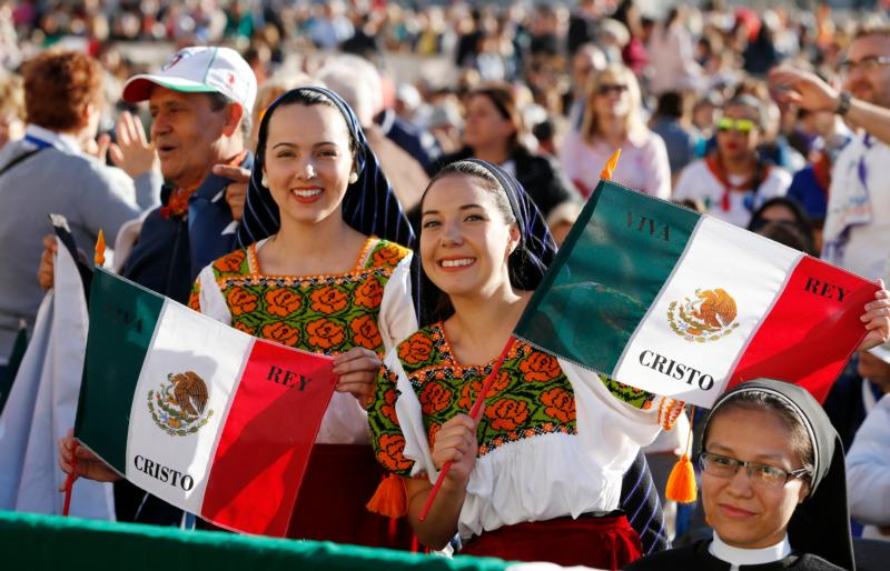 Women in traditional Mexican dress hold flags before the canonization Mass for seven new saints celebrated by Pope Francis in St. Peter's Square at the Vatican Oct. 16. Mexican St. Jose Sanchez del Rio was among those canonized. (CNS photo/Paul Haring) See POPE-CANONIZATION Oct. 16, 2016.