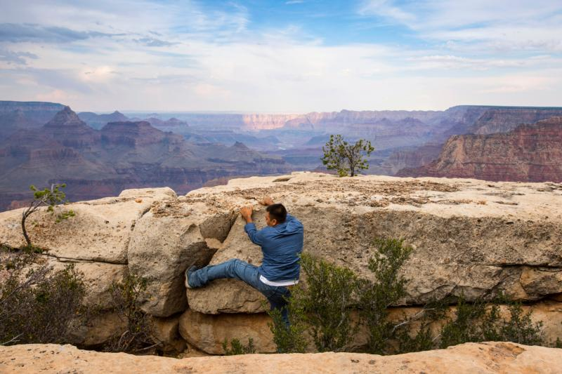 A man climbs a rock outcrop on the south rim of the Grand Canyon in Arizona Aug. 20. The National Park Service warns visitors to stay at least six feet from the edge, yet many people take risks for better views and photos. (CNS photo/Nancy Wiechec) See NPS-CENTENNIAL-CATHOLIC-HISTORY Oct. 17, 2016.