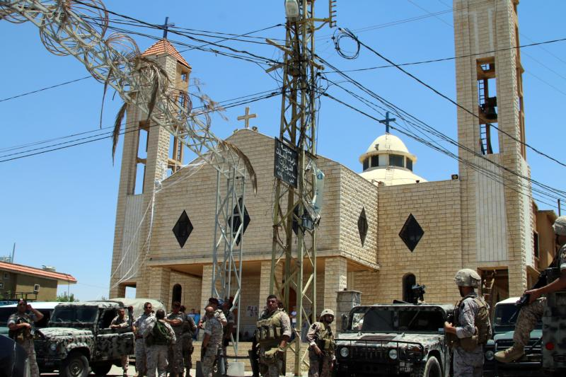 Lebanese army soldiers stand on an armored truck next to a church during a patrol after bombings in late June in Qaa. When a series of bombs exploded in the Lebanese Christian village near the Syrian border, it not only changed the lives of the victims and their families, but also the lives of Syrian refugees living nearby. (CNS photo/EPA) See QAA-SYRIANS-RESTRICTIONS Oct. 18, 2016.
