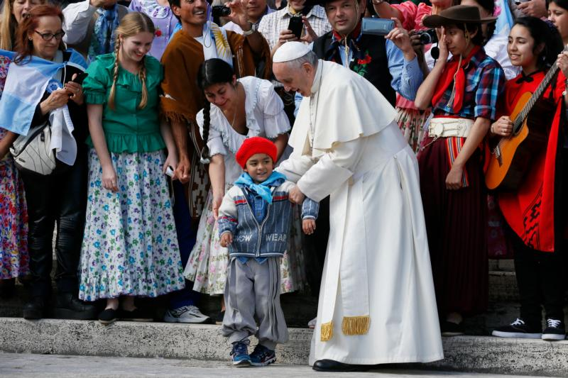 Pope Francis positions a boy for a photo as he meets an Argentine group during his general audience in St. Peter's Square at the Vatican Oct. 19. (CNS photo/Paul Haring) See POPE-AUDIENCE-HUNGRY Oct. 19, 2016.