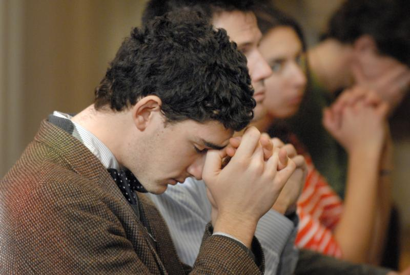 A young man prays during a novena in 2010 at The Catholic University of America in Washington. The Knights of Columbus is urging its members and other U.S. Catholics to pray a novena from Oct. 30 to Nov. 7, the eve of Election Day. (CNS photo/Rafael Crisostomo, El Pregonero) See ELECTION-KNIGHTS-NOVENA Oct. 24, 2016.
