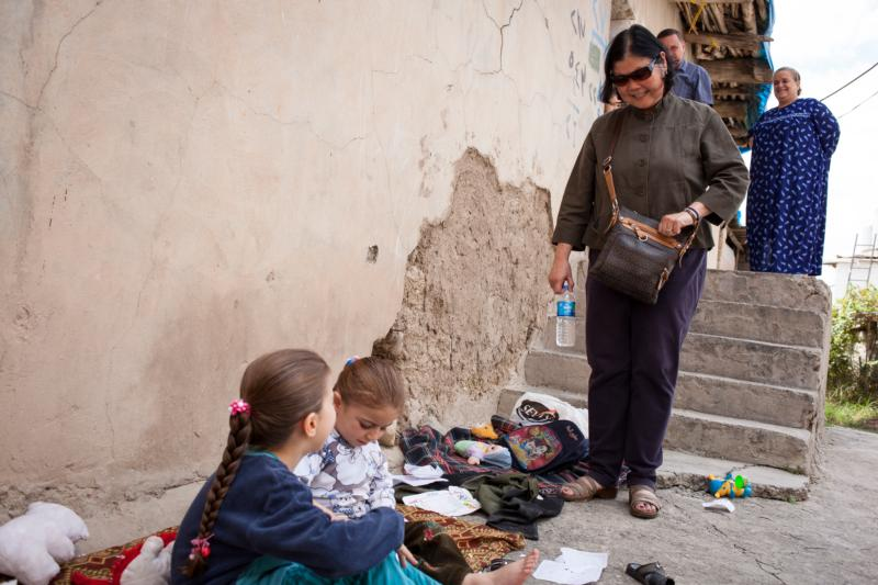 Carolyn Woo, the outgoing CEO of Catholic Relief Services, approaches two girls on a street in Duhok, Iraq, a town where many women and children were relocated after Islamic State troops overran their home villages, in this Oct. 10, 2015, photo. Woo will end her five-year term as CEO of CRS at the end of 2016. (CNS photo/Rawsht Twana, courtesy Catholic Relief Services) See WOO-CRS-RETIRE and WOO-CRS-BUSINESS Oct. 27, 2016.