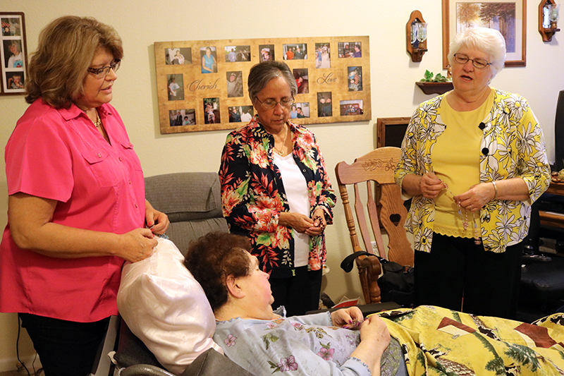 From left to right, Gemma White, Mary Salazar and Teresa Hayes pray the rosary with Mary Strecker. Salazar and Hayes are volunteers with Most Pure Heart of Mary's aging ministry. White is Strecker's daughter. LEAVEN PHOTO BY MARC ANDERSON